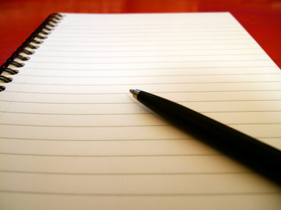 A pen rests on a blank pad of writing paper - perfect for sharing your reflections, thoughts, and feelings.