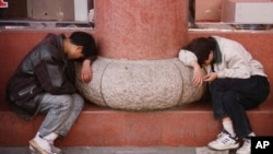 Two Chinese men take a lunch-time rest in the old part of Shanghai, Sunday Nov. 16, 1997. (AP Photo/Paola Vanzo)